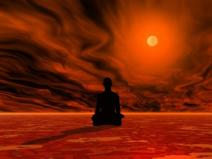 Man meditating on red ground in front of burning sun